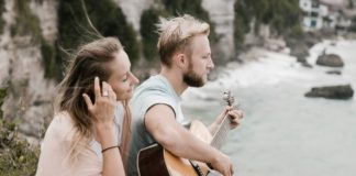 peaceful young couple playing guitar on hill against waving 4571762